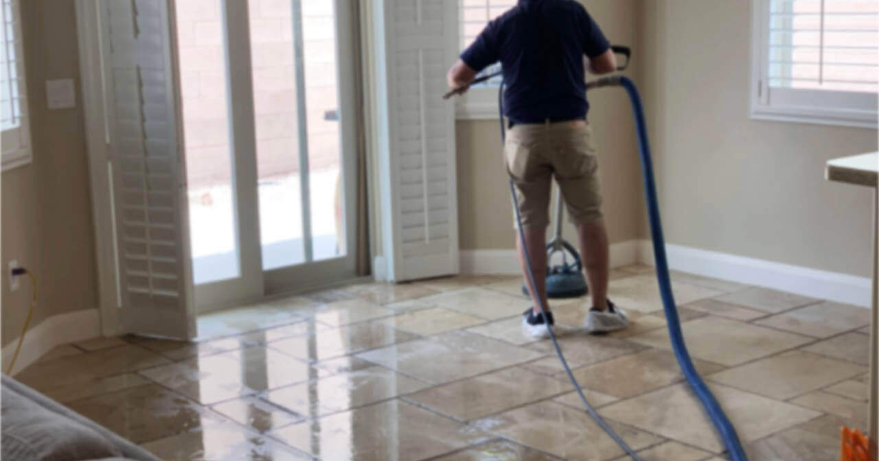 Man scrubbing tiles with a machine to clean the floor and grout in saint george, ut